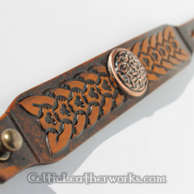 This leather cuff features an embossed Celtic Tri-Weave design with a center concho. It has been hand stained to give it a beautiful, rich look. It is made from hand selected full grain vegetable tanned leather. It is handmade in the USA. This leather armband by Celtic Leatherworks fits wrist sizes 7 - 9 inches.