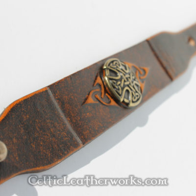 This leather cuff features an embossed Celtic Triquertra design with a center concho. It has been hand stained to give it a beautiful, rich look. It is made from hand selected full grain vegetable tanned leather. It is handmade in the USA. This leather armband by Celtic Leatherworks fits wrist sizes 7 - 9 inches.