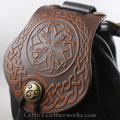 This is a custom colored Celtic Dragon Heads Sporran. It is a Rob Roy style sporran with an Interchangeable Flap. The bag is made from black deertanned leather. The flap is full grain vegetable tanned leather with a fearsome Celtic style dragon heads embossed into it.