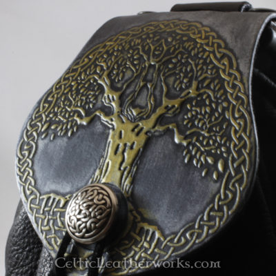 This is a custom colored Celtic Tree of Life Sporran. It is a Rob Roy style sporran with an Interchangeable Flap. The bag is made from black deertanned leather. The flap is full grain vegetable tanned leather embossed with The Tree of Life. It has been custom colored to have a distressed steel and brass finish.