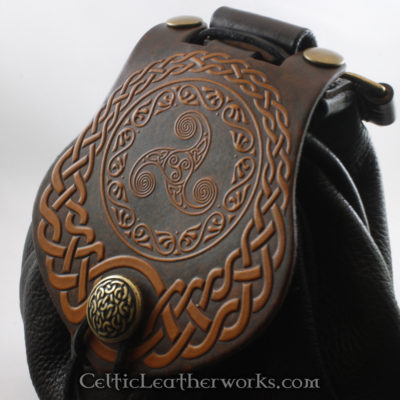 This is a custom colored Triskele Sporran. It is a Rob Roy style sporran with an Interchangeable Flap. The bag is made from black deer tanned leather. The flap is full grain vegetable tanned leather with a mystical, swirling triskele embossed into it.