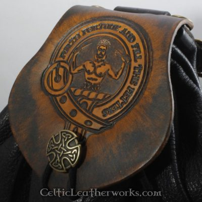 This is a custom colored Clan Murray Sporran. It is a Rob Roy style sporran with an Interchangeable Flap. The bag is made from black deer tanned leather. The flap is full grain vegetable tanned leather with the Murray clan crest embossed into it.