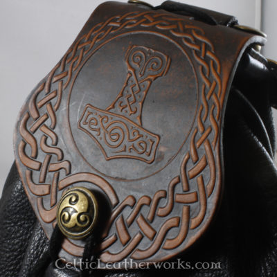 This is a custom colored Mjolnir Sporran. It is a Rob Roy style sporran with an Interchangeable Flap. The bag is made from black deer tanned leather. The flap is full grain vegetable tanned leather with Thor's hammer Mjolnir embossed into it. It has been hand stained to have a distressed brown finish.