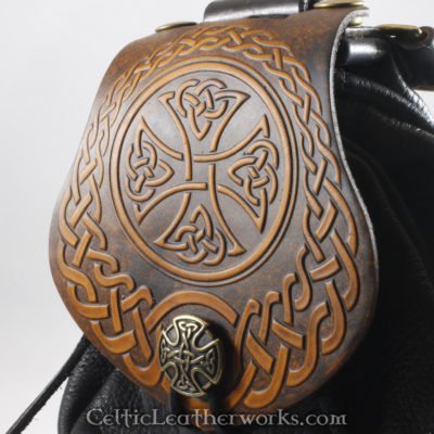 This is a custom colored Carolingian Cross Sporran. It is a Rob Roy style sporran with an Interchangeable Flap. The bag is made from black deer tanned leather. The flap is full grain vegetable tanned leather with an impressive Celtic Cross embossed into it.